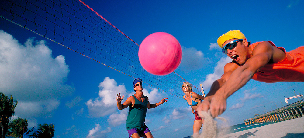 Young couple playing beach volleyball