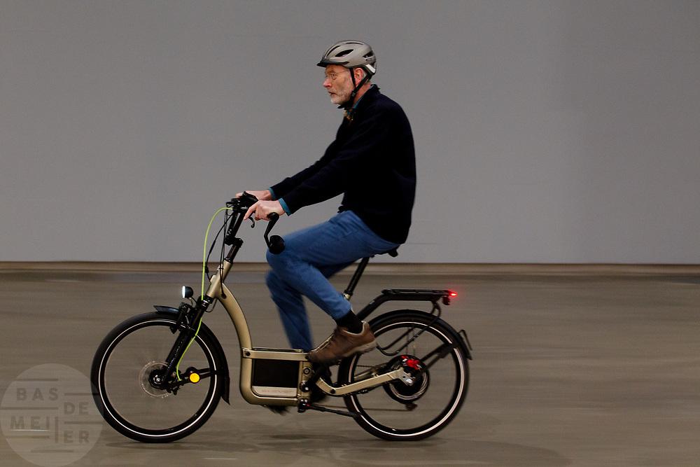 Een oudere man probeert een e-bike. In Utrecht wordt in de Jaarbeurs de Fiets- en Wandelbeurs samen met de E-bike Experience gehouden. De beurs richt zich op actieve buitensportvakanties. Fietsers en wandelaars kunnen informatie vinden over materieel en reizen, lezingen volgen en het een en ander uitproberen.<br /> <br /> In Utrecht at the Jaarbeurs the Cycling and Walking Fair is held. The exhibition focuses on active outdoor holidays. Cyclists and hikers can find information on equipment and trips, lectures and follow a few things to try.