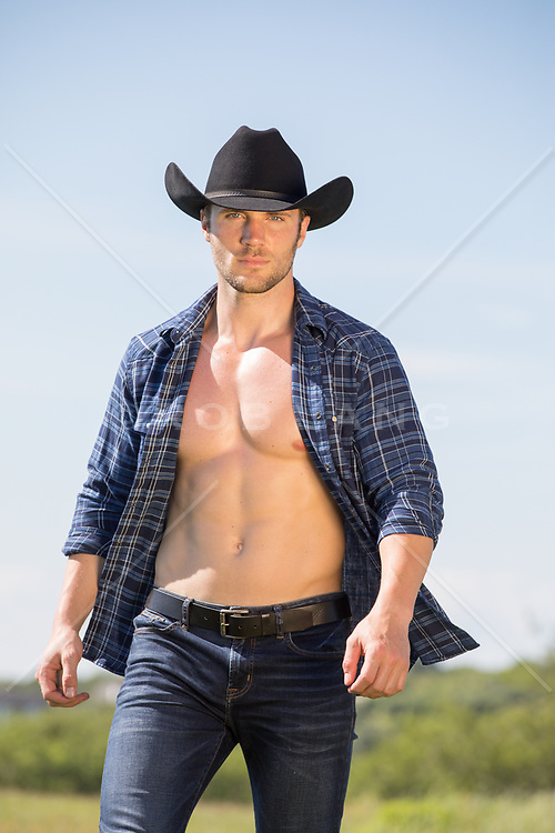 hot cowboy in open shirt walking through a field