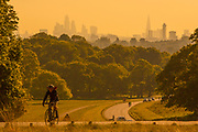 UNITED KINGDOM, Richmond Park: 14 May 2019 <br /> An early morning cyclist make his way through Richmond Park in front of the London skyline this morning as the sun rises on another fine day of weather across The UK. Temperatures are set to reach 19C in the capital and potentially higher in the Midlands.