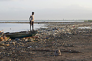 July 8, 2012 - A young girl stands on the bow of a fishing boat docked on the shoreline of Cité Soleil at dawn in Haiti. Many children are expected to help family members fetch water, repair nets or sort through the fishing catch as the day begins.<br />