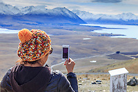 A woman taking a panorama of the landscape with her iPhone, from the Mt John Observatory, Tekapo, New Zealand