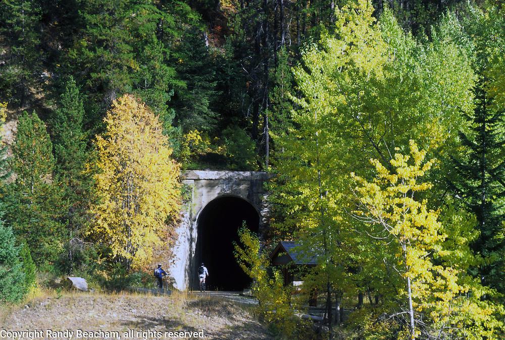 Bicyclists entering train tunnel on Hiawatha Rails to Trails path. Bitterroot Mountains, Benewah County, North Idaho