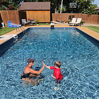 Gina Fremont gives a high five to one of her swimming lesson students Noah Massengill during his lesson.