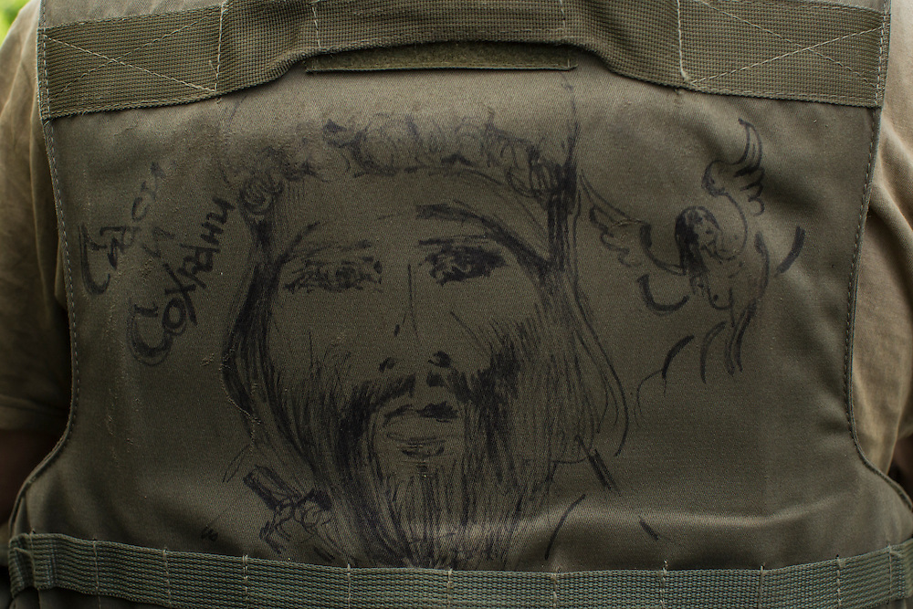AVDIIVKA, UKRAINE - JULY 9, 2016: A Ukrainian soldier with a picture of Jesus drawn on his body armor in Avdiivka, Ukraine. The town is now one of the most active areas of fighting along the line of control between the Ukrainian government and Russian-backed rebels. CREDIT: Brendan Hoffman for The New York Times