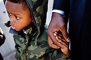"Gibran Meadows 4, left, holds his father Othello Meadows' hand as they wait in line to see President Obama speak on Wednesday, January 13, 2016, at Baxter Arena in Omaha, Neb. ""I think my son and sons that look just like him are entered into a world that in many cases is very hostile and so him being able to see the highest office in the land manned by someone that looks like him is really powerful,"" Meadows said."