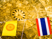11 JANUARY 2015 - BANGKOK, THAILAND:  The ceiling of a chapel with the Dhamma (left) and Thai flags at Wat Dhamma Mongkol in Bangkok. Wat Dhamma Mongkol, (pronounced 'Dhammamongkon') is on the edge of Bangkok, and visible from a number of places, especially from the elevated expressways around the city. The temple was started in the early 1960s by a revered monk who had spent more than 20 years in a forest retreat. The 95 meter high tower, completed in 1985, is a modern rendition of the tower that now marks the place of the Buddha's enlightenment in Bodhgaya, India. There are classrooms, a museum and meditation area inside the tower. The largest Buddha statue carved from a single piece of jade is on the temple grounds.   PHOTO BY JACK KURTZ