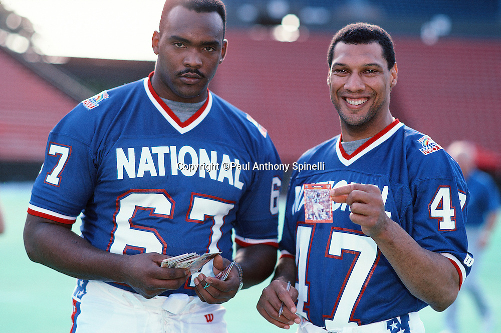 Phoenix Cardinals offensive tackle Luis Sharpe (67) and Minnesota Vikings safety Joey Browner (47) exchange trading cards during photo day the week of the 1990 NFL Pro Bowl between the National Football Conference and the American Football Conference on Jan. 30, 1990 in Honolulu. The NFC won the game 27-21. (©Paul Anthony Spinelli)