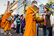 01 JANUARY 2014 - BANGKOK, THAILAND: Anti-government protestors present Buddhist monks with food, flowers and donations during a merit making ceremony at the protest camp. Thousands of anti-government protestors are camped out at Democracy Monument in central Bangkok protesting against the government of Yingluck Shinawatra. The protest leader, Suthep Thaugsuban, has called for residents of the Thai capital to rise up against Yingluck. He has promised to shut the city of 12 million down in his final push to overthrow the government. About 100 members of the Thailand's Buddhist clergy visited the protest site Wednesday morning for a New Year's Day special merit making ceremony for the protestors.     PHOTO BY JACK KURTZ