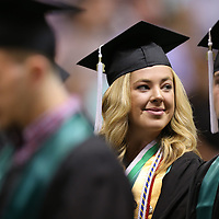 Madelyn Lindsey smiles to classmates as they take their seat on the row behind her as Mooreville High School begins their graduation Saturday.