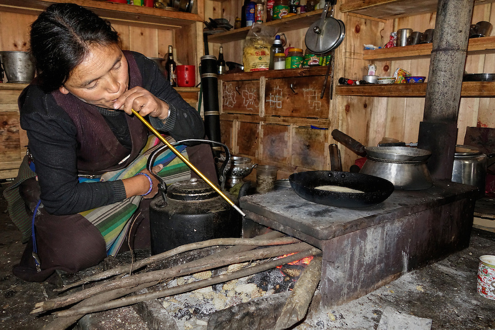 Tibetan woman blowing through a tent pole to stoke the fire in a wood stove, Tsum Valley, Nepal.