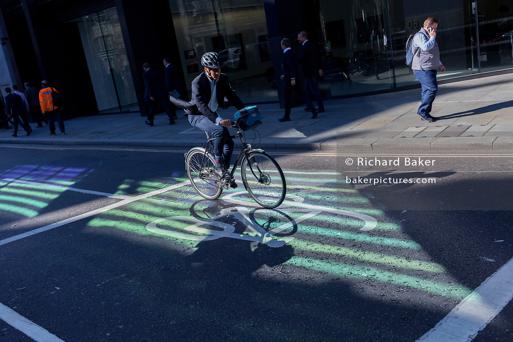 In an area of reflected light, a cyclist pedals along Threadneedle Street in the City of London - the capital's financial centre (aka The Square Mile), on 27th September 2018, in London, England.