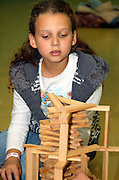 young female Children of 6 building with Kapla wooden construction blocks, the KAPLA plank, only one size, is best adapted for building without gluing or fixing.