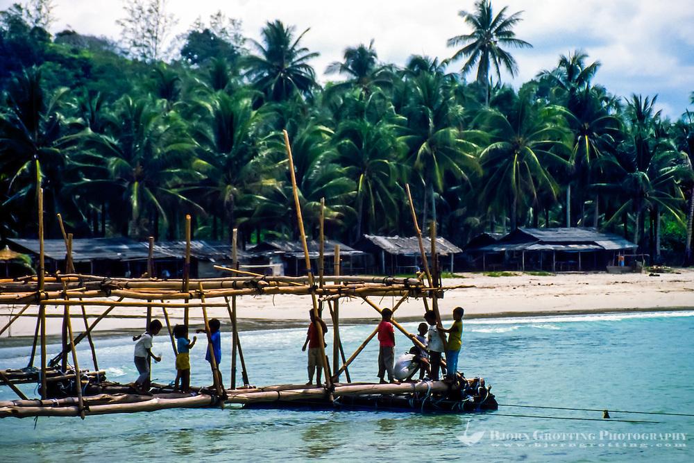 Riau Islands, Bintan. Kids playing outside a small village on Trikora Beach.