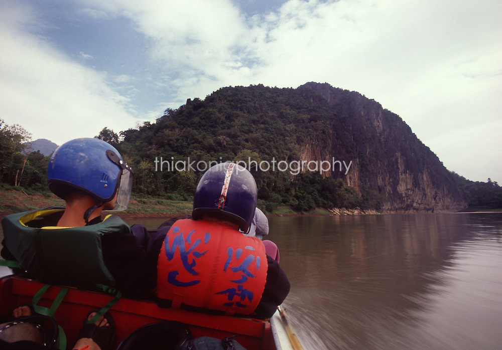 View from behind of two tourists in a fast boat up the Nam Ou river, with Chinese lifejackets and helmets.