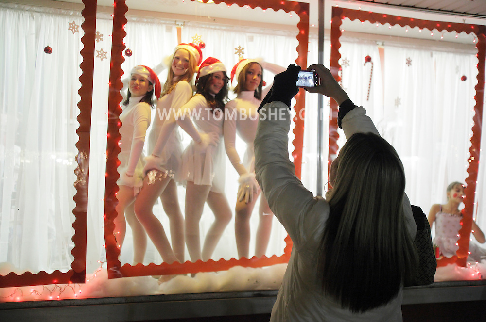 Pine Bush, New York - A woman takes a picture of dancers from the Mitchell Performing Arts Center pose in a storefront window during the Pine Bush Festival of Lights on Dec. 4, 2010. ©Tom Bushey / The Image Works