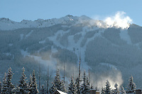 Blackcomb Mountain during a sunny winter day, snowmaking clouds rise near the top of the mountain.