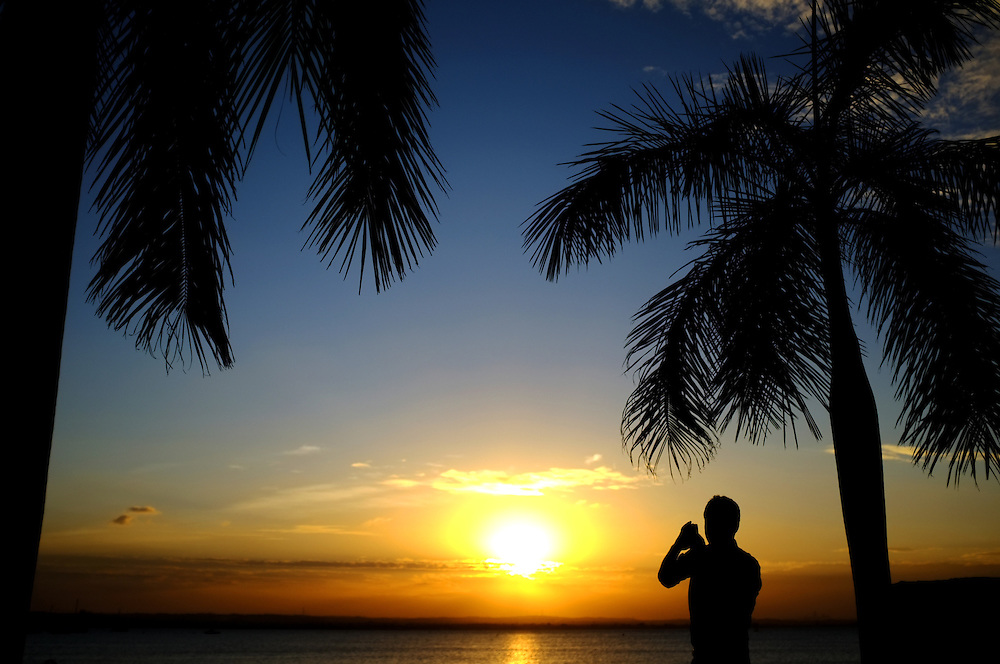 DAR ES SALAAM, TANZANIA - 13-07-24 -  A man photographs sunset over the Indian Ocean on July 24 in Dar es Salaam, Tanzania.  Photo by Daniel Hayduk
