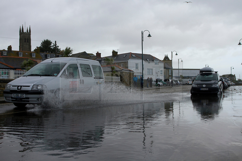 © Licensed to London News Pictures. 15/08/2012. Penzance, UK. A taxi drives through a flood along Penzance Promenade. The Police closed the road due to waves crashing over the road but many motorist ignored the warnings. Photo credit : Ashley Hugo/LNP