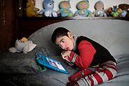 Napoli, Italia - Francesco mentre guarda cartoni animati sul letto della sua stanza a Napoli.