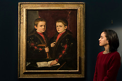 "© Licensed to London News Pictures. 02/12/2016. London, UK. A staff member views ""Portrait of two boys, said to be Members of the Pesaro Family"" by Tiziano Vecellio, called Titian, (est. GBP 1-1.5m), at a preview of Sotheby's upcoming Old Masters Evening Sale in New Bond Street. Photo credit : Stephen Chung/LNP"