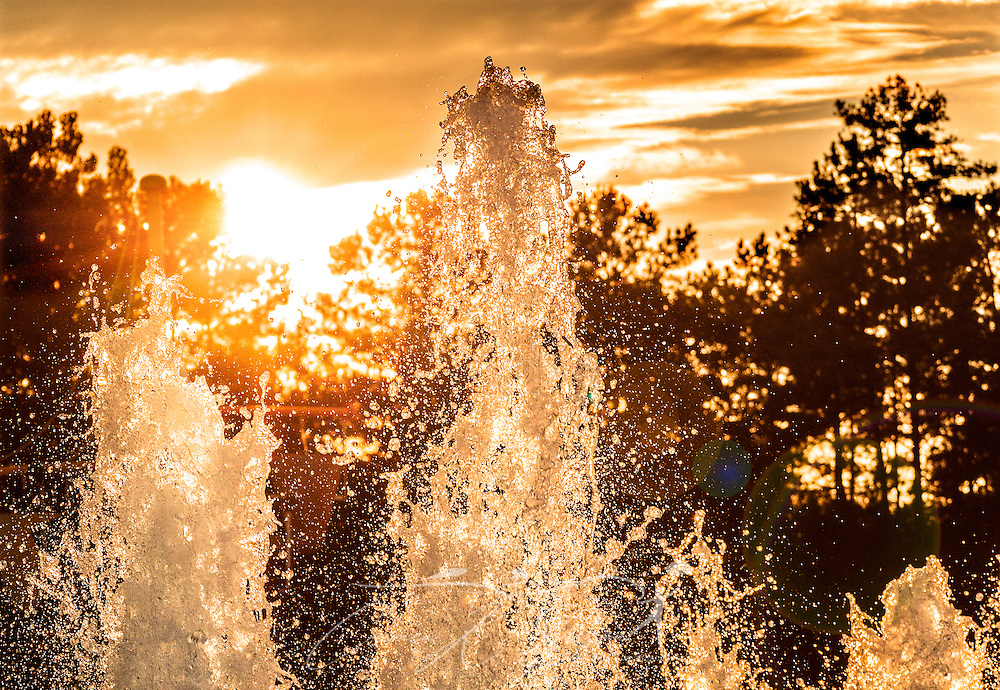 The sun sets behind fountains of water at Browns Mill Family Aquatic Center, July 9, 2014, in Lithonia, Georgia. The community pool, located in the Stone Mountain area, is open seven days a week and offers a variety of options for adults and children looking for a fun way to beat the summer heat. (Photo by Carmen K. Sisson/Cloudybright)