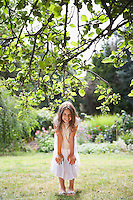 Girl (10-12) smiling in garden