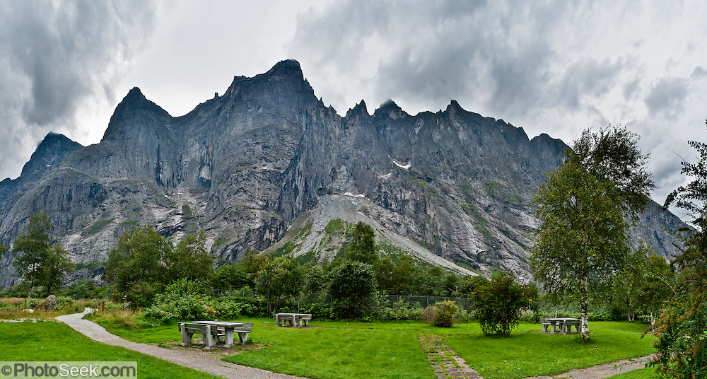 The Troll Wall is the tallest vertical rock face in Europe, about 1100 meters (3600 feet) from base to summit. Located within Reinheimen National Park, the Troll Wall (Trollveggen) and Trolltindane (Troll Peaks) soar high above the Romsdalen valley near Åndalsnes, Norway. The gneiss rock summit ridge overhangs its base by nearly 50 meters (160 ft). Parachute BASE jumping from Troll Wall has been illegal since 1986, but climbing the face is allowed, as is hiking up the gentler back. Trollveggen is in Rauma municipality, Møre og Romsdal county. Panorama stitched from 7 overlapping photos.
