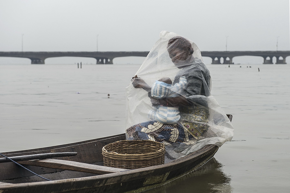 A mother breastfeeds her daughter beneath a plastic sheet to protect her on a rainy day.