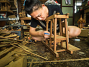 02 NOVEMBER 2016 - BANGKOK, THAILAND:  GOB, who now runs the family spirit house workshop, measures the interior of a spirit house she's making. There used to be 10 families making traditional spirit houses out of teak wood in Ban Fuen, a community near Wat Suttharam in the Khlong San district of Bangkok. The area has been gentrified and many of the spirit house makers have moved out, their traditional wooden Thai houses replaced by modern apartments. Now there is just one family making the elaborate spirit houses. The spirit houses are made by hand. It takes three days to make a small one and up to three weeks to make a large one. Prices start at about $90 (US) for a small one. The largest, most elaborate ones can cost over $1,000 (US). Almost every home and most commercial buildings in Thailand have a spirit house, which is a shrine to the protective spirit of a the land. Spirit houses are also common in Burma, Cambodia, and Laos.       PHOTO BY JACK KURTZ