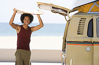 Man with surfboard by camper van
