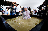 A Christian Ethiopian Orthodox worshipper immerses himself in a big plastic container filled with water pumped out from the Jordan River during Orthodox Epiphany celebrations on January 18, 2010 at the Qasr al-Yahud baptismal site in the West Bank. Thousands of Orthodox Christians braved rain on the banks of the Jordan river to plunge into plastic tubs filled with its murky water in a celebration of Jesus's baptism..© ALESSIO ROMENZI