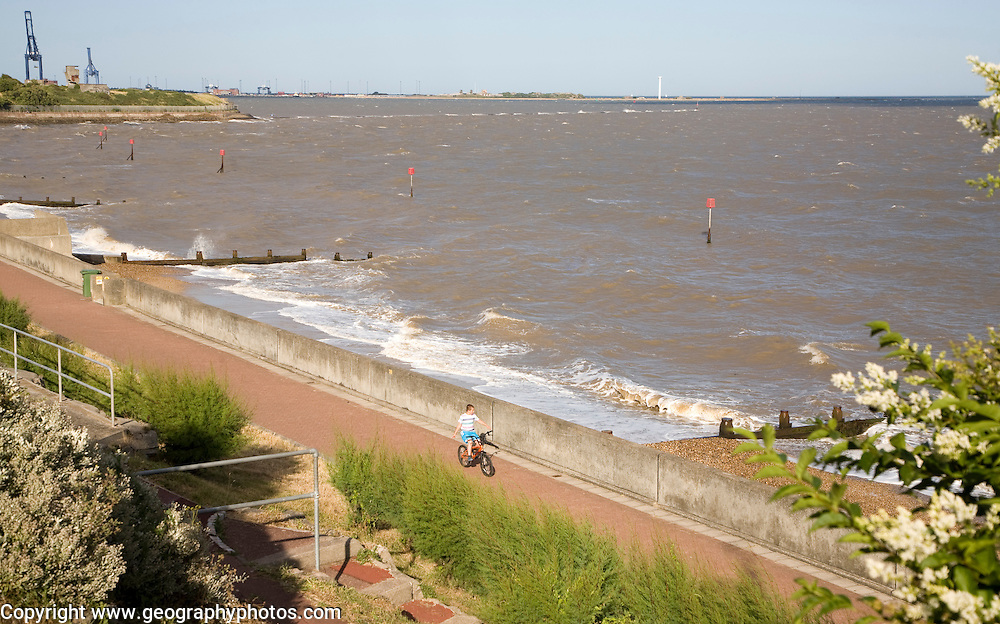 Boy cycling along the seafront in windy weather at Dovercourt, Harwich, Essex, England