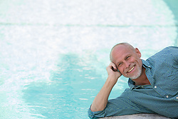 good looking mature man enjoying time outdoors by a pool