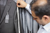 Tailor measuring suit's sleeve