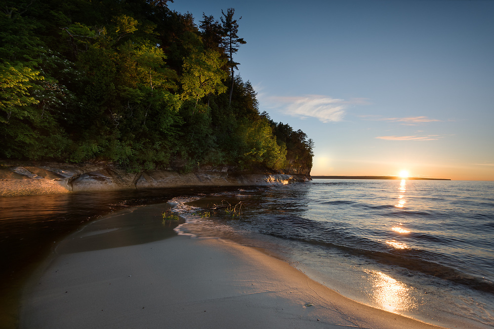 The light from a summer sunset illuminates the treetops above Miner's River outlet.  Pictured Rocks National Lakeshore