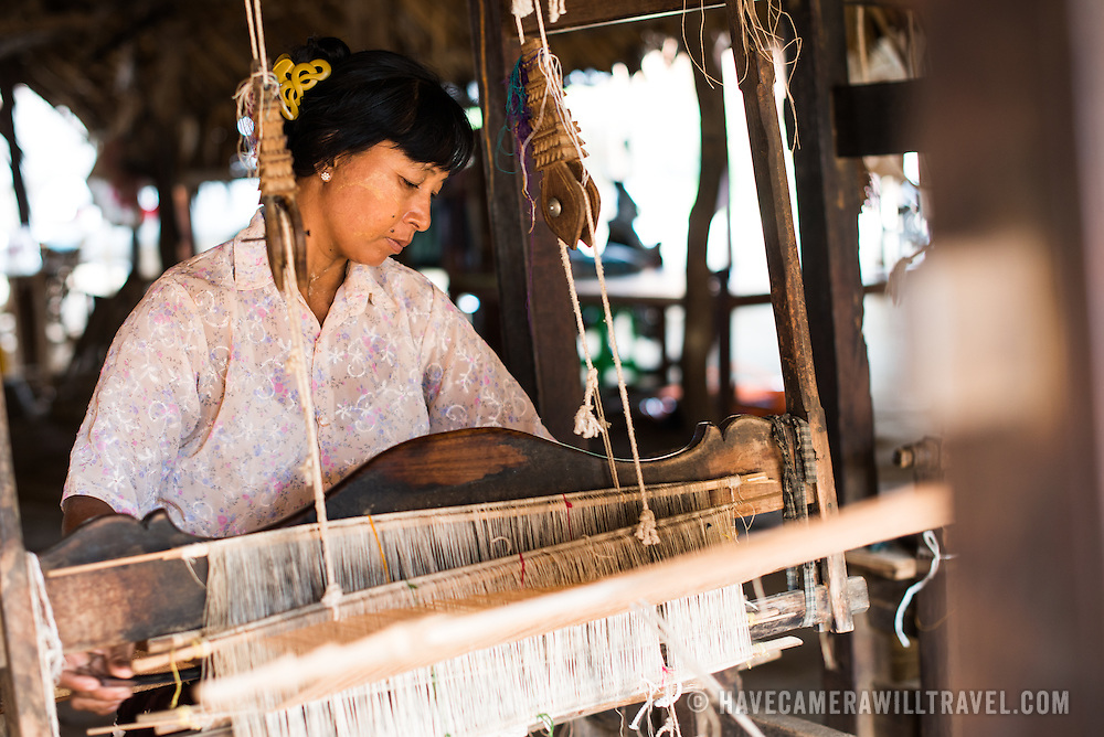 A woman uses a traditional loom to weave textiles in Minnanthu Village in Bagan, Myanmar. Set amidst the archeological ruins of the Plain of Bagan, the tiny Minnanthu Village retains the traditional way of life.