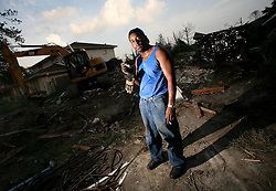 29 August 2006. New Orleans, Louisiana. Lakeview. <br /> The one year anniversary of hurricane Katrina. Demolition man Jay Johnson of east Orleans stands in the rubble of what used to be an upscale upper middle class home he has just torn down. Johnson picked through the rubble for the copper piping to recycle. He was on speakerphone to the lead contractor who was moaning about his labor force and problems with crews, his 'boss' having just returned from yet another first class jet set holiday with all the cash he is now earning.<br /> Photo Credit©; Charlie Varley/varleypix.com