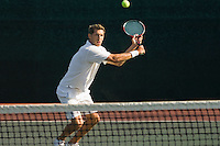 Tennis Player squatting on tennis court Hitting Backhand over net