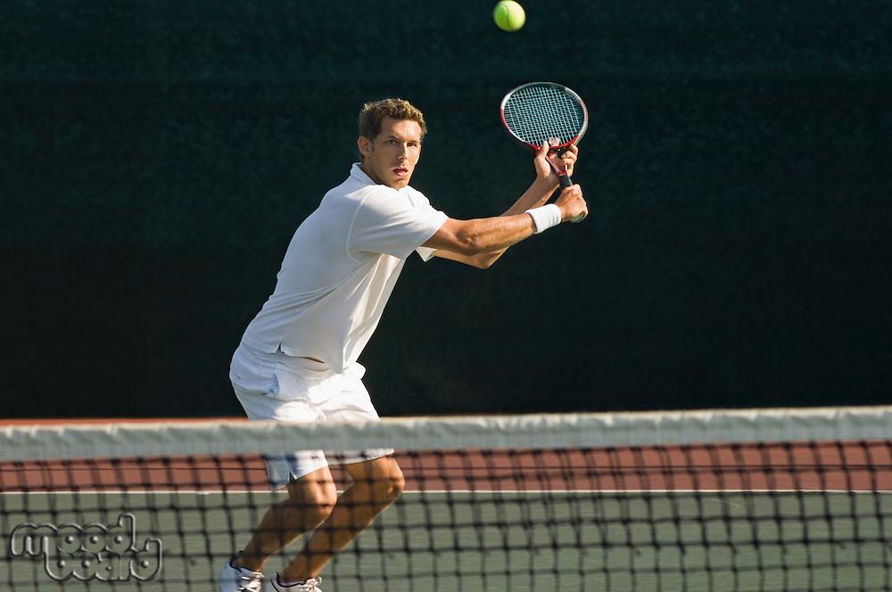 Tennis Player squatting on tennis court Hitting Backhand over net