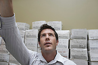 Business man standing in front of stack of filing boxes in storage room reaching up low angle view