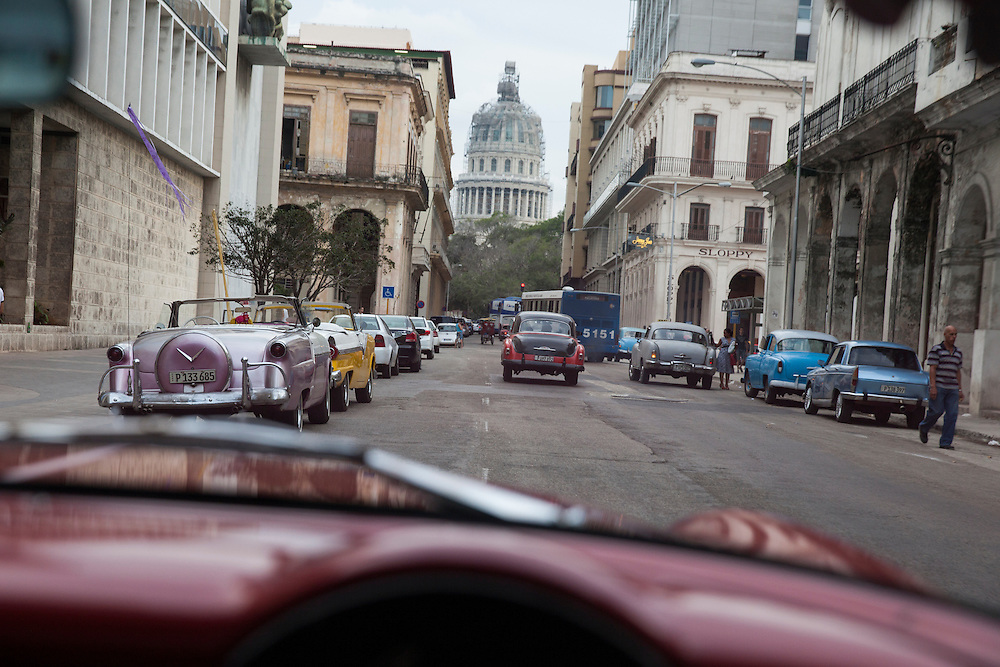 Traffic at Agramonte Street in Old Havana, Cuba, with the Capitol in the background.<br />