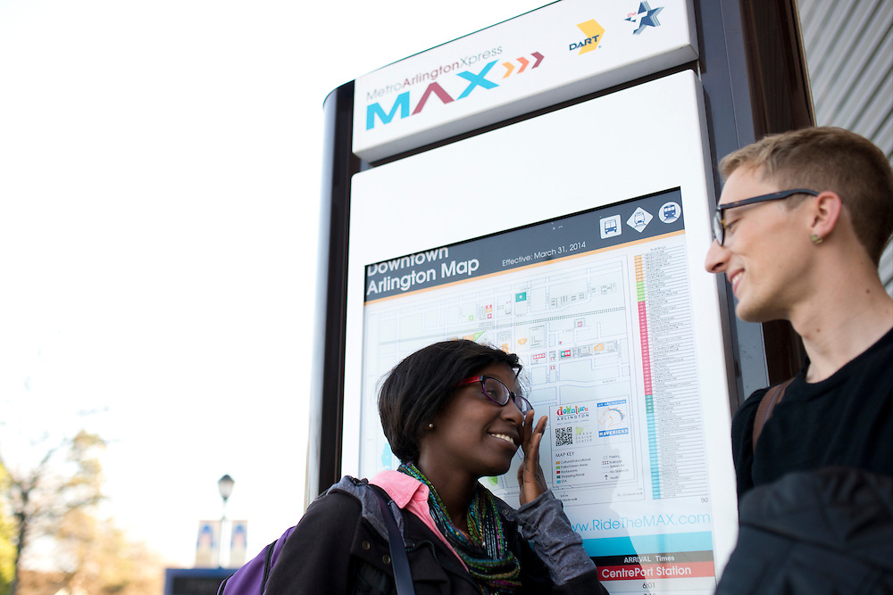 Lois Ndungu waits for the Metro ArlingtonXpress with Mason Bryant at the UT Arlington bus stop in Arlington, Texas on March 31, 2014. (Cooper Neill / The Texas Tribune)