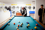 Eduardo Barajas (right) watches his father Roberto play pool as the two wait for clothes to dry at Coin Laundry in East Point, Georgia December 30, 2009. Monica, Eduardo's mother, has been separated from her husband and son so she could continue dialysis in Mexico.