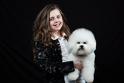 © Licensed to London News Pictures. 10/03/2016. Birmingham, UK. Maisie Hall with her Bichon Frise named Maggie at Crufts 2016 held at the NEC in Birmingham, West Midlands, UK. The world's largest dog show, Crufts is this year celebrating it's 125th anniversary. The annual event is organised and hosted by the Kennel Club and has been running since 1891. Photo credit : Ian Hinchliffe/LNP