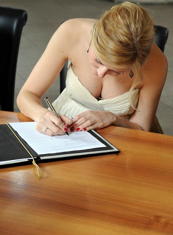 Junge Braut unterzeichnet Ehevertrag auf dem Standesamt |     young bride signs a marriage contract       |