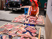 18 JULY 2013 - BANGKOK, THAILAND:  A woman makes jerky in the Onnuch (also known as On Nut) Wet Market off of Sukhumvit Soi 77 in Bangkok.       PHOTO BY JACK KURTZ