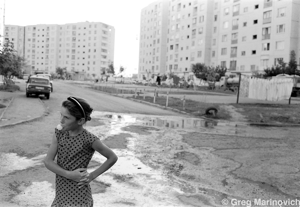 A young girl blows bubblegum as she waits for her turn to collect water, Grozny, Chechnya. 1995. Greg Marinovich