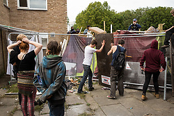 A police officer observes housing activists constructing a barricade on the Sweets Way housing estate close to the home of its last surviving resident, Mostafa Aliverdipour, on 23rd September 2015 in London, United Kingdom. A group of housing activists calling for better social housing provision in London had occupied some of the properties on the 142-home estate in Whetstone, in some cases refurbishing properties intentionally destroyed by the legal owners following eviction of the original residents, in order to try to prevent or delay the eviction of Mr Aliverdipour and the planned demolition and redevelopment of the entire estate by Barnet Council and Annington Property Ltd.