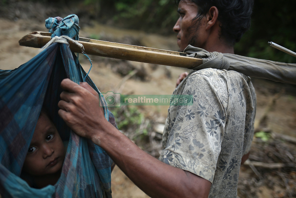 September 5, 2017 - Cox'S Bazar, Bangladesh - A Rohingya child is carried on a sling while his family walks up a hill after crossing the border into Bangladesh near Cox's Bazar's Teknaf area, Tuesday. A total of 87,000 mostly Rohingya refugees have arrived in Bangladesh since violence erupted in neighbouring Myanmar on August 25, the United Nations said today, amid growing international criticism of Aung San Suu Kyi. Around 20,000 more were massed on the border waiting to enter, the UN said in a report. (Credit Image: © Mushfiqul Alam/NurPhoto via ZUMA Press)